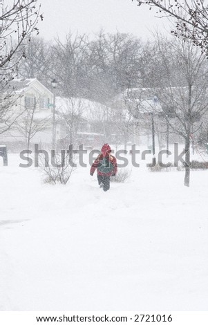 boy with backpack walking in snow storm - stock photo