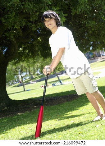 Boy (10-12) with baseball bat outdoors, portrait - stock photo
