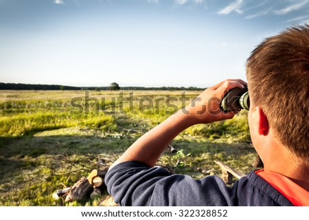 boy with binoculars exploring field area. concept for future, discovery, exploring and education - stock photo