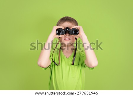 Boy with binoculars isolated on green background with copyspace. Kid looking through binoculars. - stock photo
