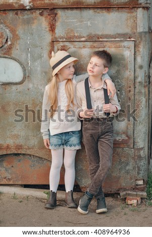 boy with blond girl with hat standing near an old metal garage - stock photo