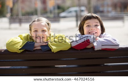 Boy with blonde girl sitting on bench outdoors in spring