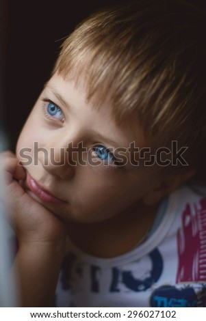 boy with blue eyes thinking while sitting by the window - stock photo