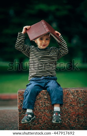boy with book on his head - stock photo