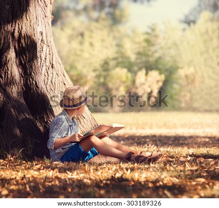 Boy with book siting under the big tree in sunny afternoon - stock photo