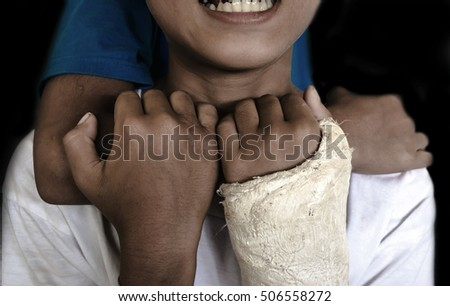 boy with broken arm is cast crying , being bullied on black background with black shadow