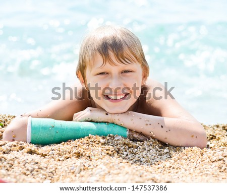boy with broken hand on sea shore - stock photo