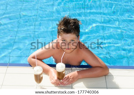 Boy with chocolate cocktail by the pool