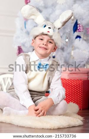 boy with Christmas gift, boy in festive costume near the Christmas tree