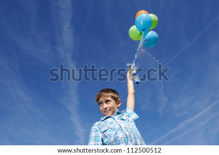 boy with colorful balloons over bright sky background - stock photo