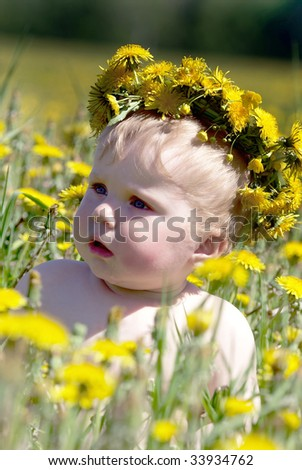 Boy with diadem from dandelions seating in spring flowers