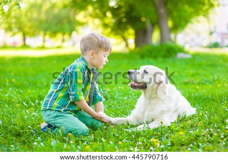 Boy with dog on green grass