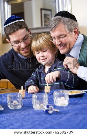 Boy with father and grandfather spinning dreidel, celebrating Hanukkah - stock photo