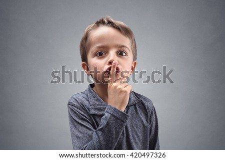 Boy with finger on lips making a silent gesture - stock photo