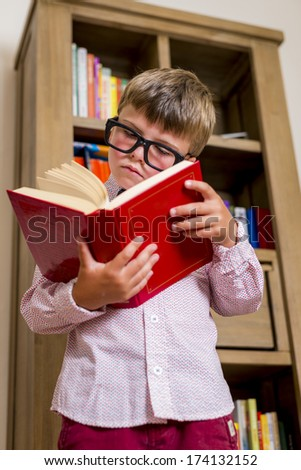 boy with funny glasses reading a book - stock photo