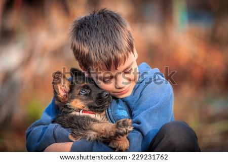 Boy with german shepherd dog puppy. - stock photo