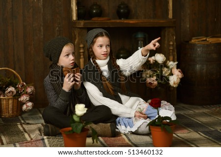 boy with girl in vintage dress sitting on the plaid in the box. looking at flowers in pots