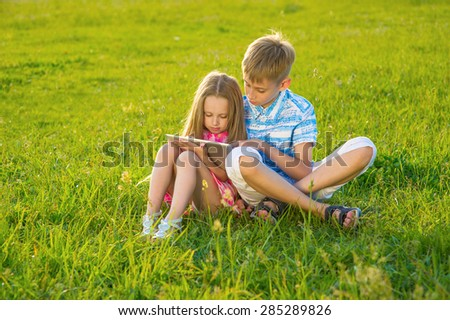 Boy with  girl sitting on the lawn and play on the tablet.