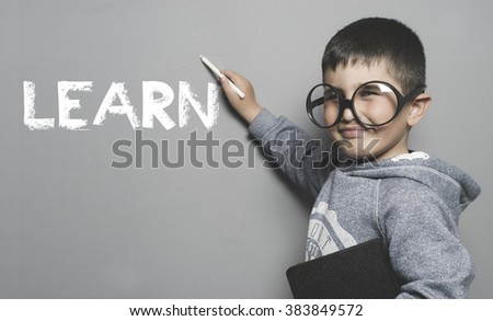 boy with glasses and funny gesture writing on the blackboard the text learn