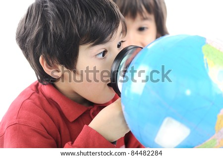 Boy with globe of earth and magnifier - stock photo