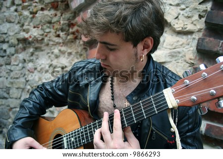 boy with guitar (finger-board in focus) - stock photo
