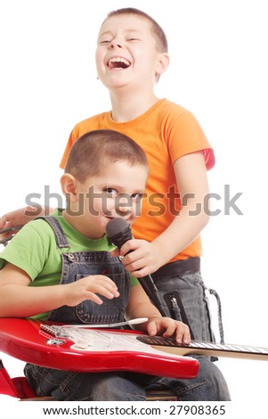 Boy with guitar singing song with laughing brother on backgroiund