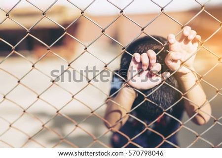 boy with hands on a fence, kid behind a metal fence