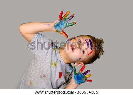 Boy with hands painted in colorful paints  - stock photo