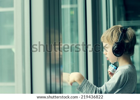 boy with headphones looking out the window at the airport - stock photo
