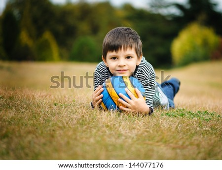 Boy with his ball in the park - stock photo