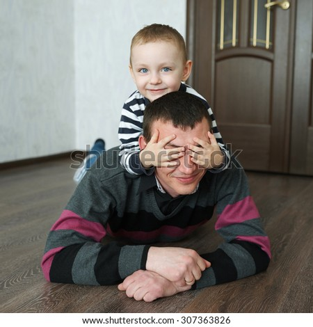 boy with his father lying on the floor at home - stock photo