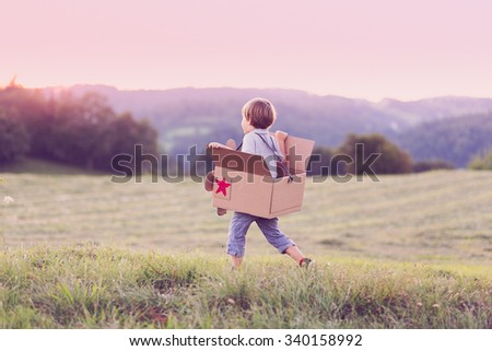 Boy with his paper plane running on a meadow, pretending he is flying - stock photo
