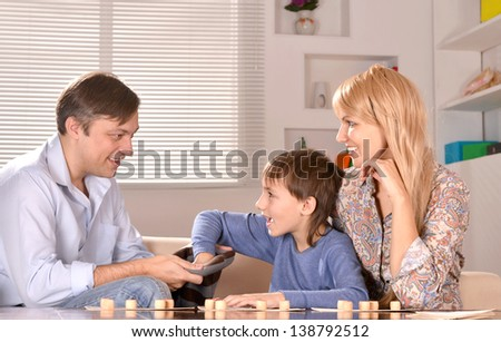boy with his parents playing lotto at home