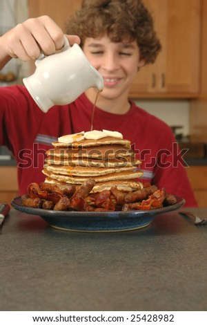 Boy with huge pancake breakfast - stock photo