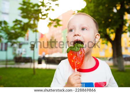 Boy with large lollipopin the park - stock photo