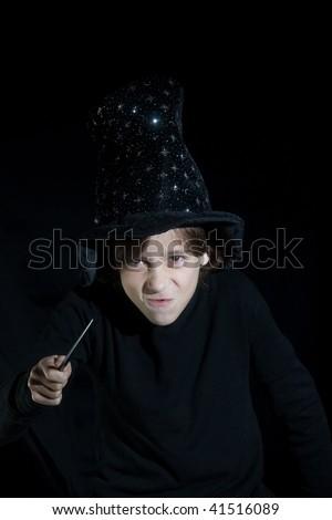 boy with magic wand on black background - stock photo