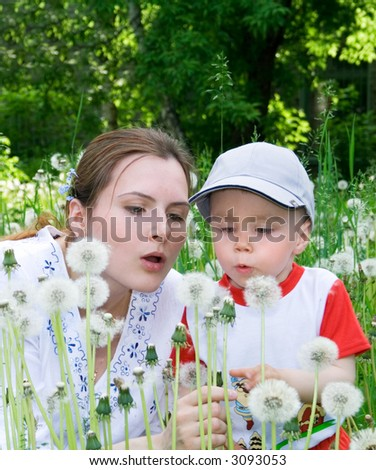 Boy with mother on the meadow. Flowers. 7 - stock photo