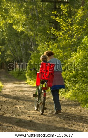 Boy with mum on a wood footpath in the solar evening - stock photo