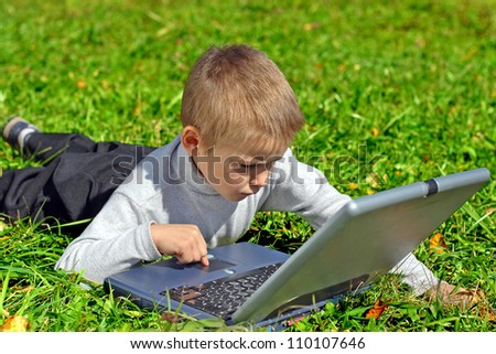 boy with notebook on the summer meadow - stock photo