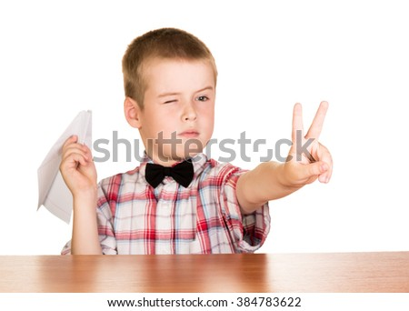 Boy with paper plane sitting at a table isolated on white background. - stock photo