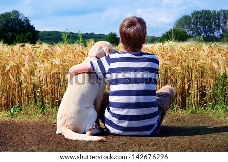 Boy with pet dog, corn field in background - stock photo