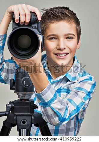 Boy with photo camera on thripod posing at studio - stock photo