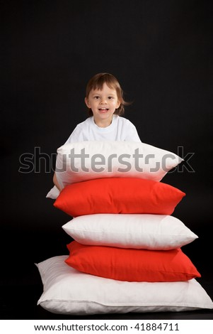 boy with pile of cushions - stock photo