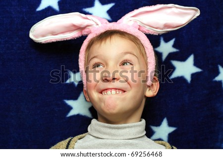 boy with rabbit ears making a funny face - stock photo