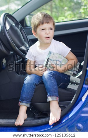 Boy with road map sits in car