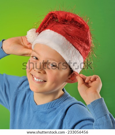 boy with Santa Claus Hat on green background, shoot in studio - stock photo