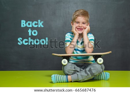 Boy with skateboard in front of school board with text BACK TO SCHOOL