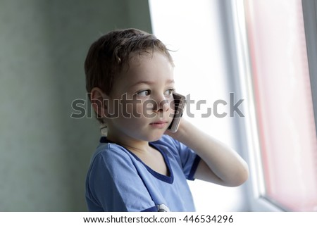 Boy with smartphone near window at home - stock photo