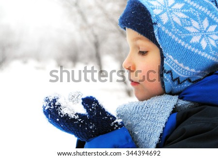 Boy with snow in his hands, New Year concept - stock photo