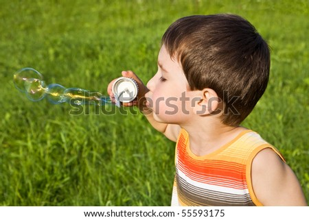 Boy with soap bubbles against a green grass - stock photo